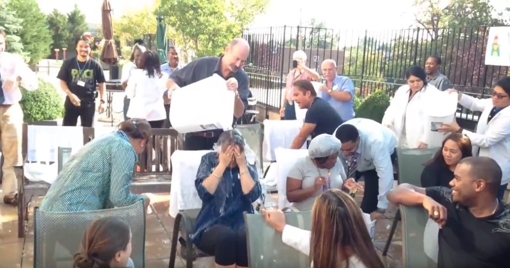 taff members seated and having buckets of ice water dumped on them