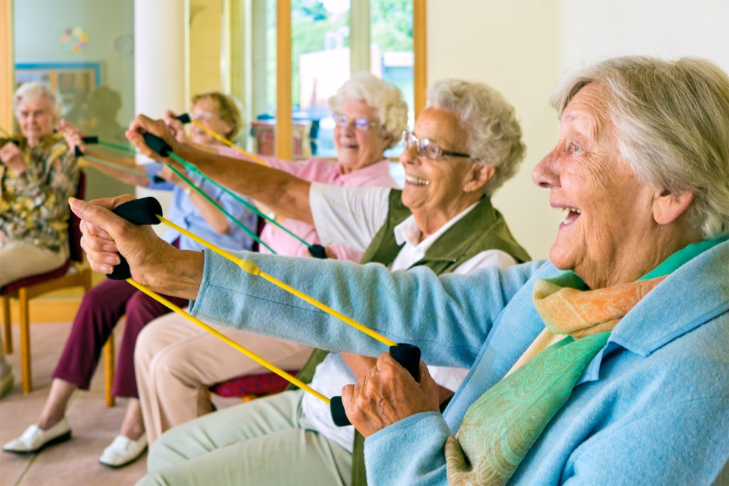 Photo of Large group of happy enthusiastic elderly ladies exercising in a gym sitting in chairs doing stretching exercises with rubber bands