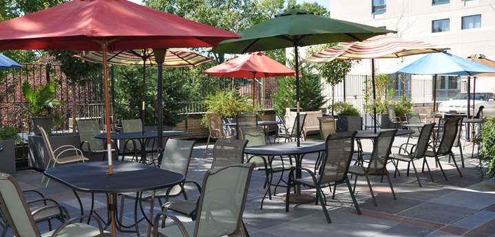 Our outdoor patio with tables and chairs and umbrells